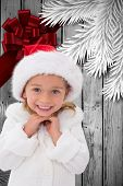 Cute little girl wearing santa hat against wood with festive bow