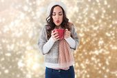 Brunette in winter clothes holding hot drink against blurred lights