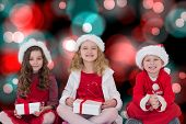 Festive little siblings smiling at camera holding gifts against digitally generated twinkling light design