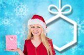 Festive blonde holding a gift bag against blurred christmas background