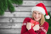 Woman holding christmas present against blurred fir branches on wood