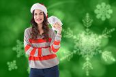 Festive brunette holding her cash against blurred christmas background