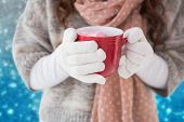 Woman in winter clothes holding a mug against blurred lights