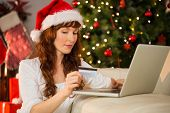 Redhead shopping online with laptop at christmas at home in the living room