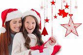 Mother and daughter opening gift against hanging red christmas decorations