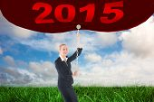 Businesswoman pulling a chain against green grass under blue sky