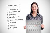 Businesswoman holding a calendar against grey card