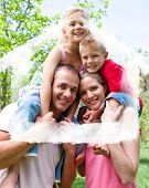 Happy parents giving their children piggyback ride against house outline in clouds