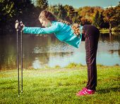 Vintage retro effect filtered hipster style image of nordic walking adventure and exercising concept - woman doing exercise with nordic walking poles in park