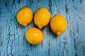 Four fresh ripe yellow lemons on blue wooden background