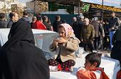 stock photo of tehran  - TEHRAN, IRAN - 13 DECEMBER 2014: Little girl drinks tea on a car on a religious holiday Arbaeen