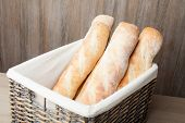 Loafs Of Traditional French Bread Baguette Stocked In Woven Basket