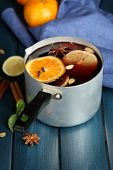 Old metal pan of tasty mulled wine on wooden table