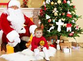 Santa Claus giving  present to  little cute girl near  fireplace and Christmas tree at home