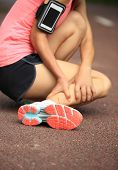 picture of ankle shoes  - young woman runner hold her twisted ankle - JPG