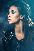 young beautiful woman portrait in black leather jacket with studs, profile, studio shot, dark background