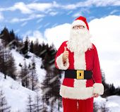 christmas, holidays, gesture and people concept- man in costume of santa claus showing thumbs up over snowy mountains background