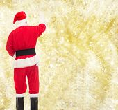 christmas, holidays and people concept - man in costume of santa claus writing something from back over yellow lights background