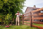 A man is cleaning wooden fence with electric power washer
