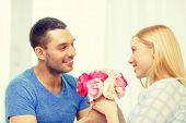 love, holiday, celebration and family concept - smiling man giving girfriens flowers at home