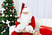 Santa Claus sitting on sofa with  gift boxes near Christmas tree