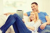 love, family, technology, internet and happiness concept - smiling happy couple witl tablet pc computer at home