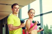 sport, fitness, lifestyle and people concept - smiling man and woman with dumbbells exercising in gym