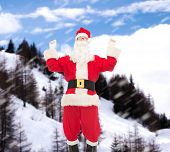 christmas, holidays and people concept - man in costume of santa claus having fun over snowy mountains background