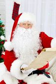 Santa Claus sitting on sofa with list of presents near Christmas tree