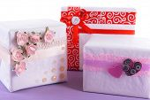 Three cute white present boxes on purple surface isolated on white
