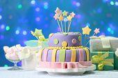 Delicious birthday cake on shiny blue background