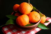 Fresh ripe mandarins on napkin, on wooden background