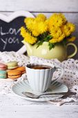 Yellow flowers in decorative teapot, cup with hot drink and tasty macaroons on wooden background