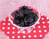 Prunes in glass bowl on polka-dot napkin on color wooden background