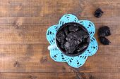 Cup filled with prunes on blue lace doily, on wooden background