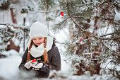 cute happy child girl plays with toy bullfinch in snowy winter forest