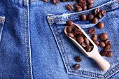 Scoop of coffee beans on the jeans background