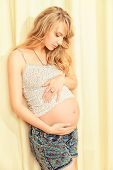 Portrait of a beautiful pregnant woman, gently touching her tummy. Healthcare. Family concept.