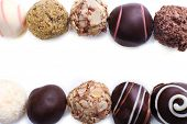 Lines of assorted chocolate candies on a white background