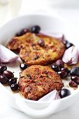 Oven-roasted pork chops with red onion and olives