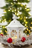 Christmas decorations with lantern and decorative wreath on fir tree background