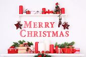 Decorations with Merry Christmas inscription on mantelpiece on white wall background