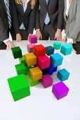 Meeting with people around a table with multicolored blocks floating around