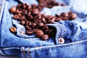 Handful of coffee beans on ripped jeans background