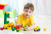 child boy playing with block toys at home
