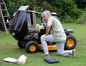 Senior Gentleman repairing his lawn mower