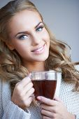 Smiling attractive woman with lovely long curly blond hair enjoying a mug of coffee as she looks at the camera with a friendly smile