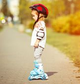 two year old pretty girl in roller skates and a helmet on the street