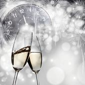 Toasting with champagne against holiday lights and clock close to midnight
