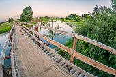 Bridge over a swampy river in sunset time. Fisheye look